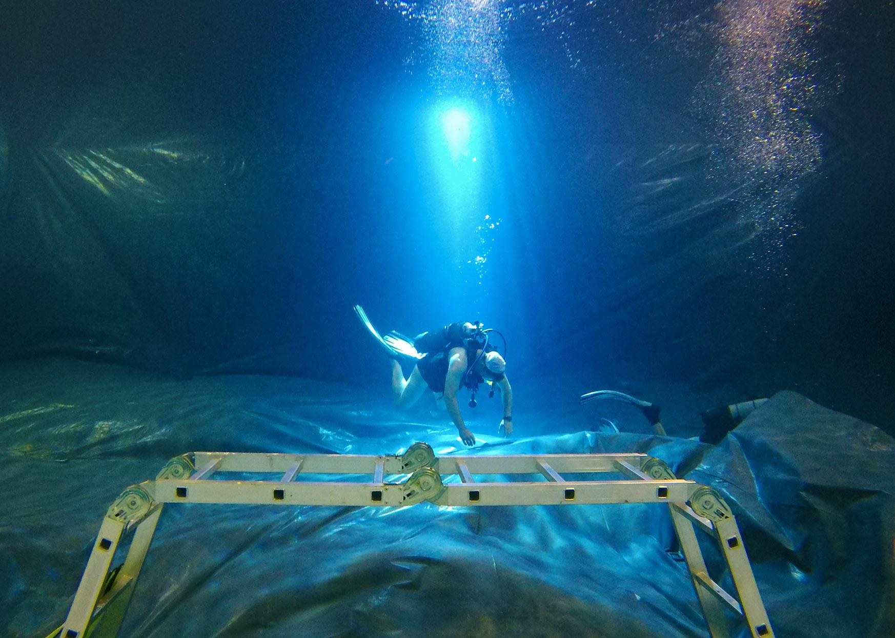 plongeur installe un bâche au fons d'une piscine